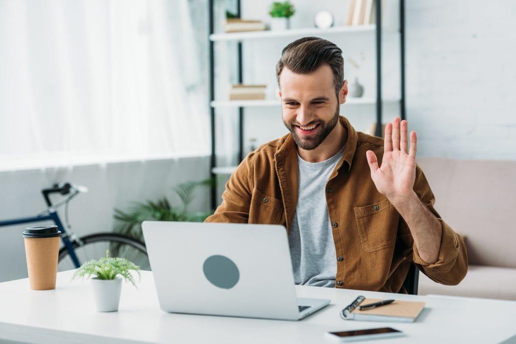 Das Bild zeigt einen Mitarbeiter, der die Talent Management Software elearnio an seinem Schreibtisch nutzt und in die Kamera des Laptops winkt