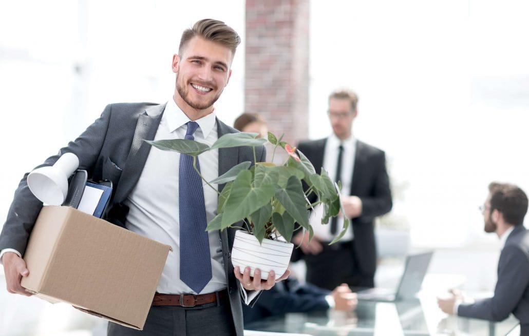 Ein neuer Mitarbeiter, der seinen ersten Tag hat und mit einer Blume und einer Kiste in sein neues Büro kommt