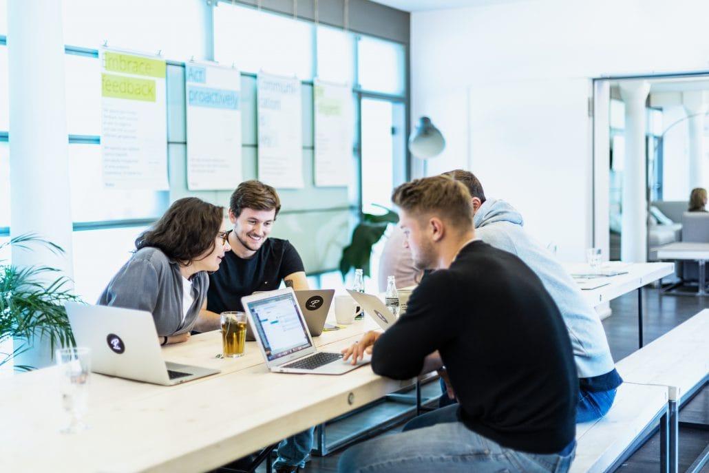 Das Bild zeigt Mitarbeiter von Personio die an einem Tisch sitzen und zusammenarbeiten